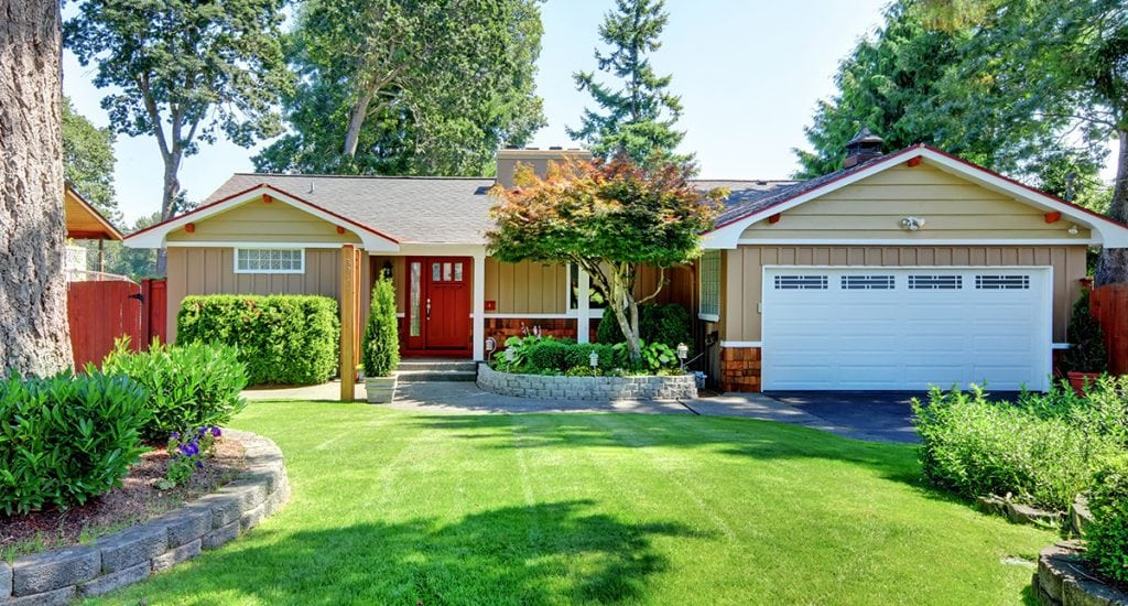 Cute small rambler house with red door and white garage door